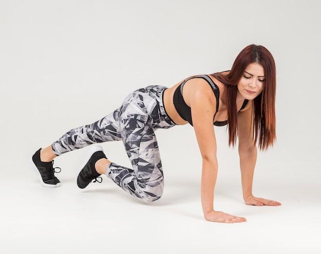 Vista lateral da mulher atlética fazendo prancha