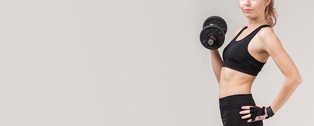 Vista lateral da mulher atlética, levantamento de peso com espaço de cópia