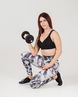 Vista lateral da mulher atlética, levantamento de peso