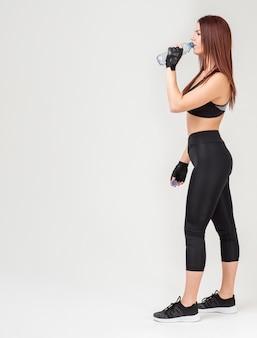 Vista lateral da mulher atlética no ginásio vestuário bebendo água