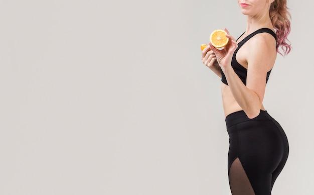Vista lateral da mulher atlética posando com uma laranja nas mãos