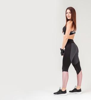 Vista lateral da mulher atlética posando enquanto usava athleisure