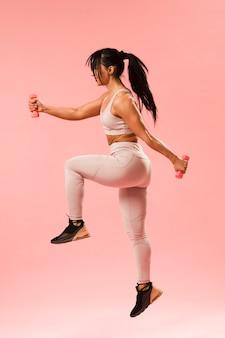 Vista lateral da mulher atlética pulando com pesos