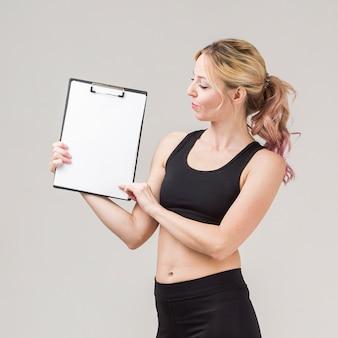 Vista lateral da mulher atlética segurando um bloco de notas em branco