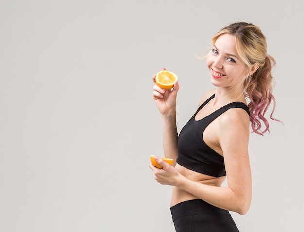 Vista lateral da mulher atlética sorridente posando com laranjas