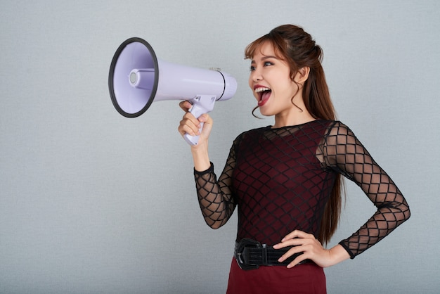 Vista lateral da mulher atraente, gritando no megafone com o braço na cintura