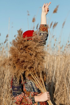 Vista lateral da mulher boêmia com o rosto coberto por grama morta