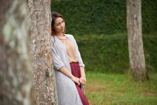 Vista lateral da mulher bonita, inclinando a árvore e olhando para longe da câmera