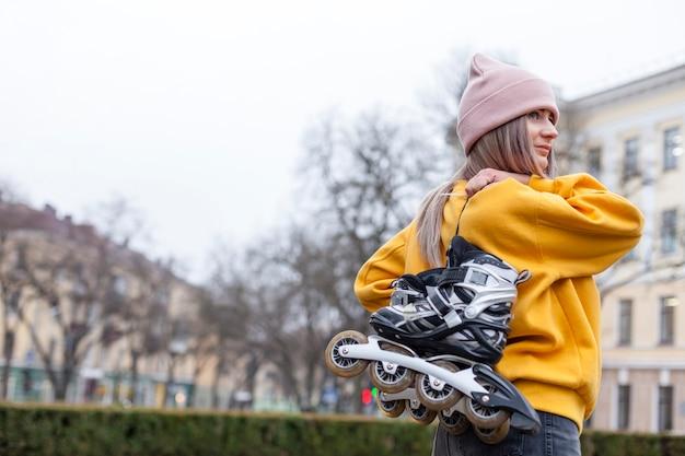 Vista lateral da mulher carregando patins
