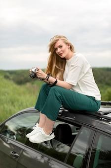 Vista lateral da mulher com a câmera em cima do carro
