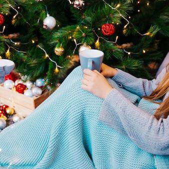 Vista lateral da mulher com caneca de chá na frente da árvore de natal
