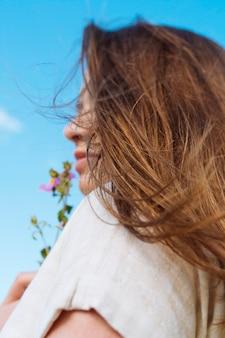 Vista lateral da mulher com flor