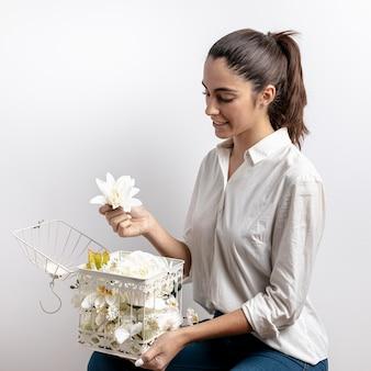 Vista lateral da mulher com gaiola de pássaro e flores