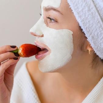 Vista lateral da mulher com máscara facial comendo morango