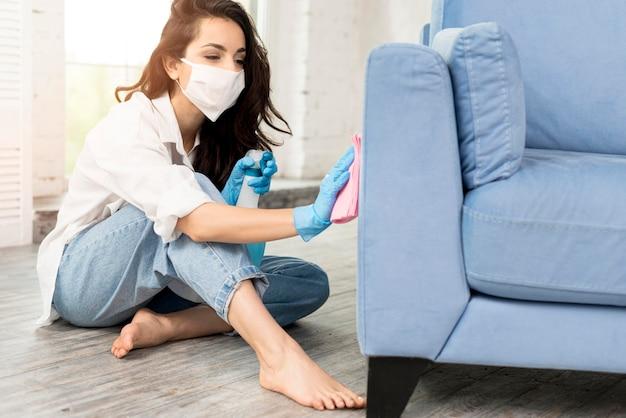 Vista lateral da mulher com máscara facial, limpeza de sofá