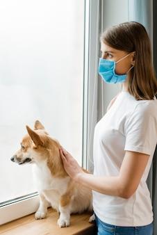 Vista lateral da mulher com máscara médica olhando pela janela com seu cachorro