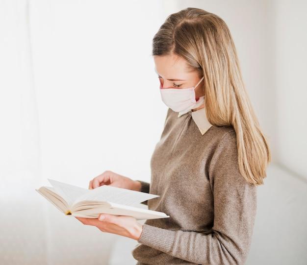 Vista lateral da mulher com máscara médica segurando e lendo o livro