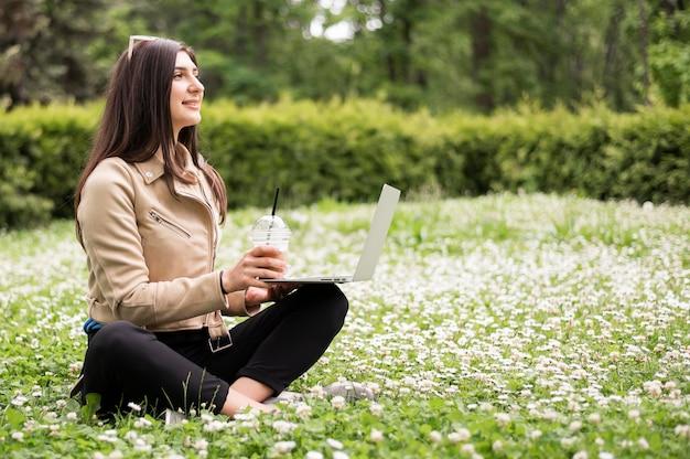 Vista lateral da mulher com o laptop ao ar livre na natureza
