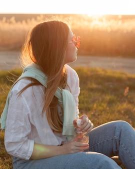 Vista lateral da mulher com óculos de sol relaxantes por do sol