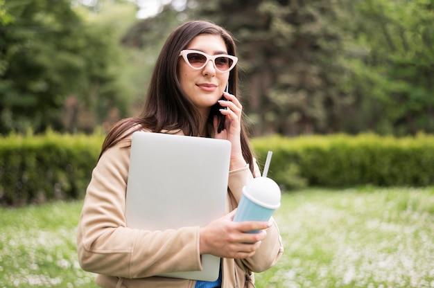Vista lateral da mulher com óculos de sol segurando laptop e beber ao ar livre