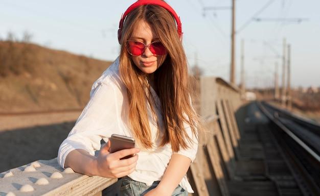 Vista lateral da mulher com óculos escuros e fones de ouvido segurando o smartphone