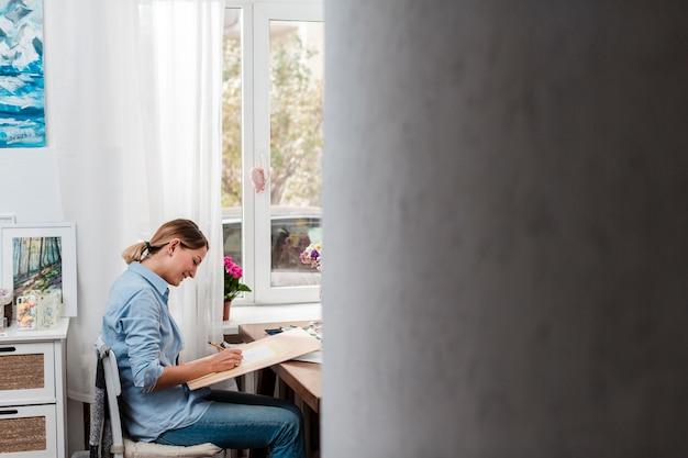 Vista lateral da mulher criativa trabalhando