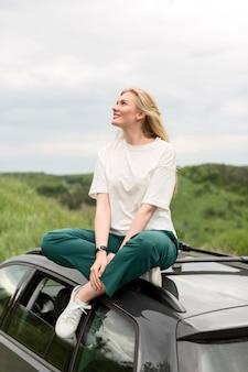 Vista lateral da mulher curtindo a natureza em pé no carro