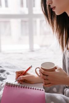 Vista lateral da mulher da colheita escrevendo no bloco de notas, tomando uma xícara de bebida quente.