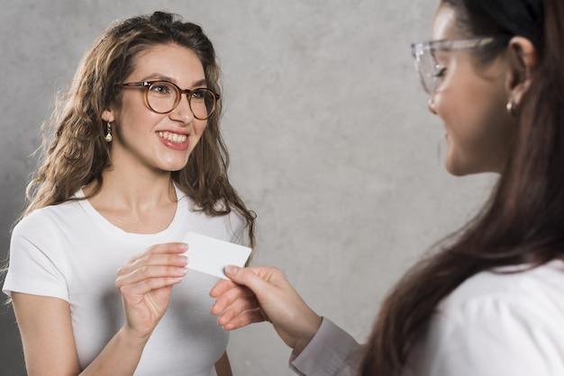 Vista lateral da mulher dando cartão de visita para potencial empregado