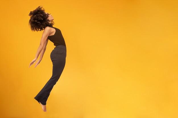 Vista lateral da mulher de cabelo afro em gravidade zero ou uma queda