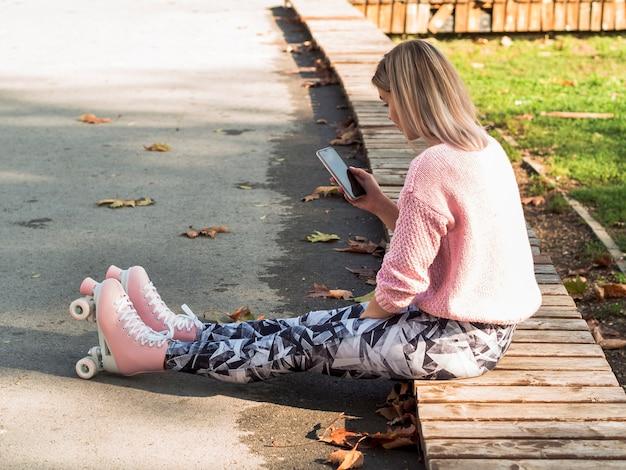 Vista lateral da mulher de caneleiras e patins segurando o smartphone