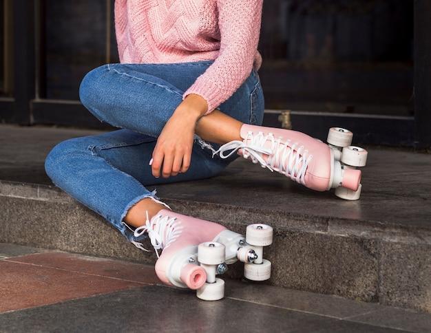 Vista lateral da mulher de jeans nas escadas com patins