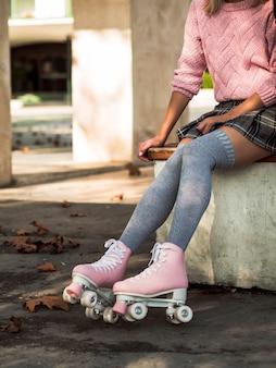 Vista lateral da mulher de meias e saia com patins