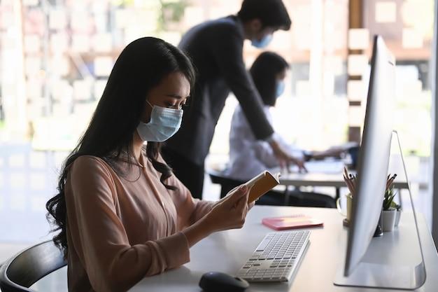 Vista lateral da mulher de negócios com máscara médica, trabalhando no escritório.