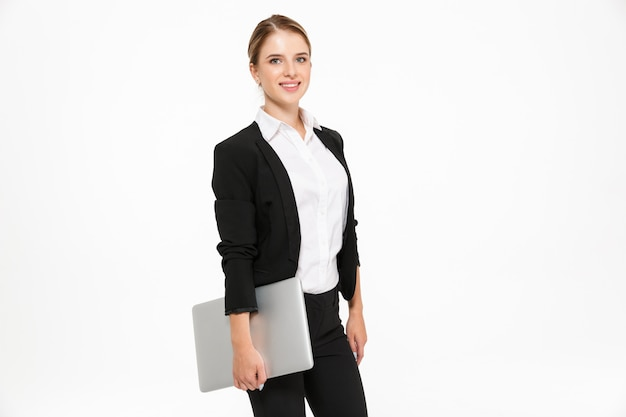 Vista lateral da mulher de negócios loira sorridente posando no estúdio com o computador portátil na mão e sobre a parede branca