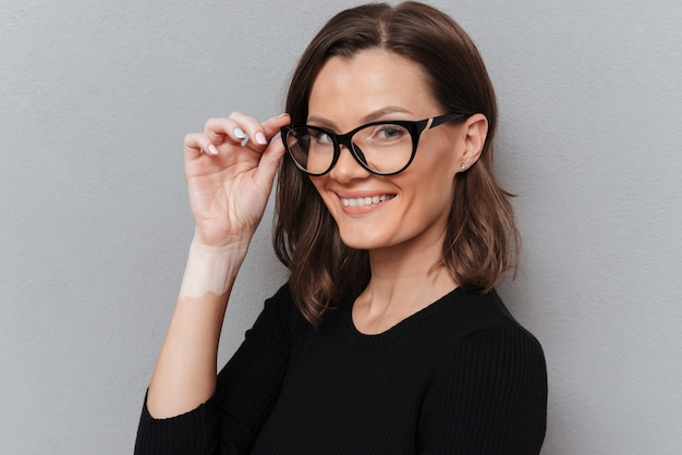 Vista lateral da mulher de negócios sorridente em óculos