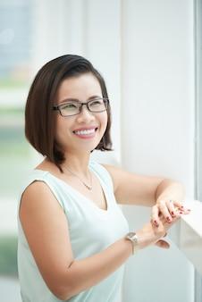 Vista lateral da mulher de óculos elegantes, olhando para a janela