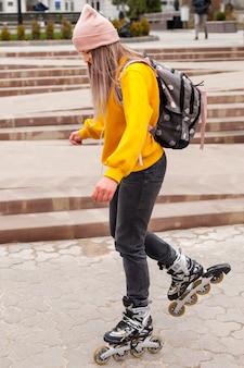 Vista lateral da mulher de patins na calçada