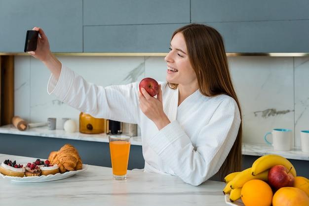 Vista lateral da mulher de roupão tomando uma selfie e segurando a maçã