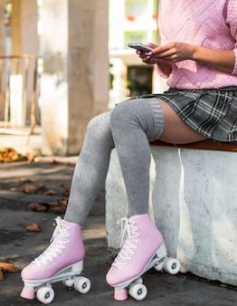 Vista lateral da mulher de saia com patins segurando o smartphone