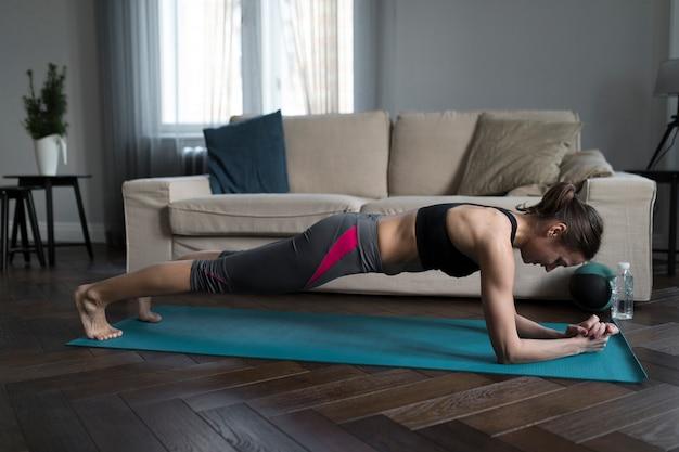 Vista lateral da mulher de tábuas no tapete de ioga