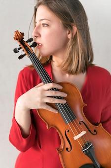 Vista lateral da mulher de vestido posando enquanto segura o violino