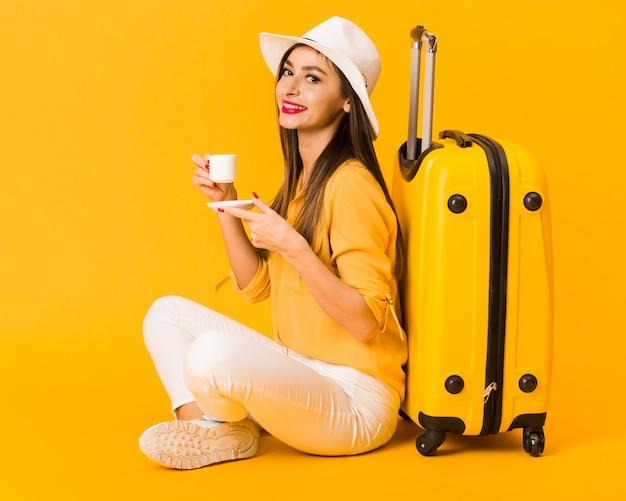 Vista lateral da mulher desfrutando de sua xícara de café ao lado de bagagem