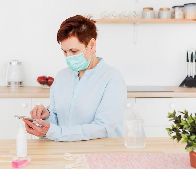 Vista lateral da mulher desinfetar o telefone enquanto usava máscara médica