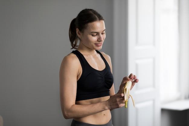 Vista lateral da mulher desportiva casca de banana