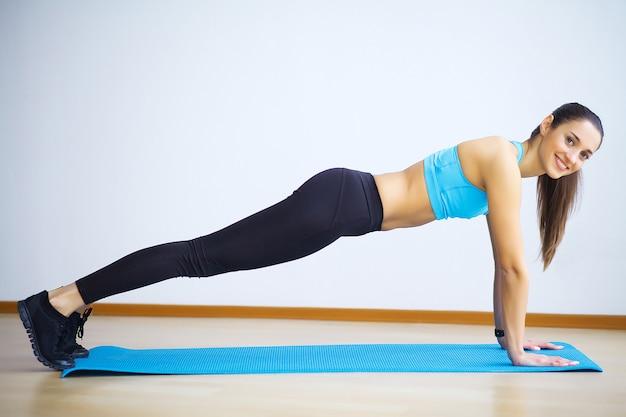 Vista lateral da mulher do ajuste que faz prancha núcleo exercício.