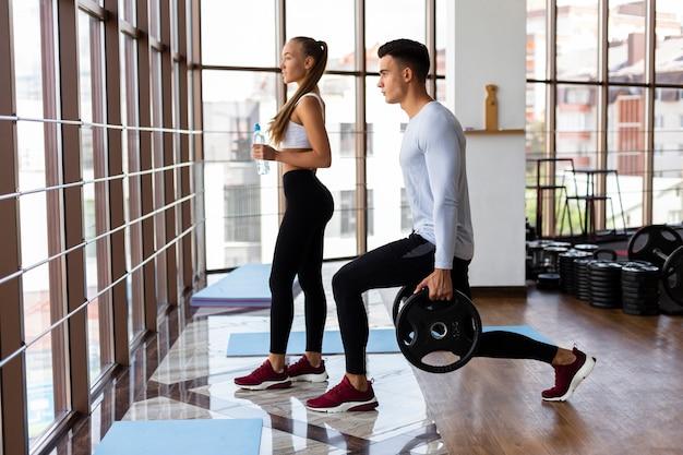 Vista lateral da mulher e do homem no ginásio