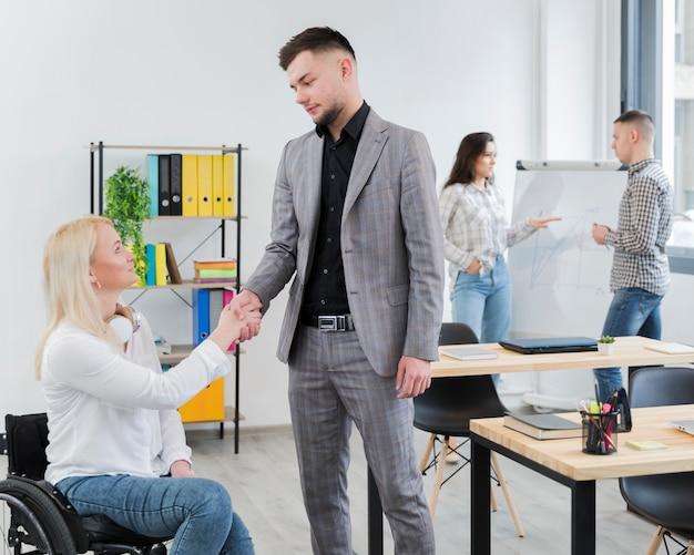 Vista lateral da mulher em cadeira de rodas, apertando as mãos com o colega