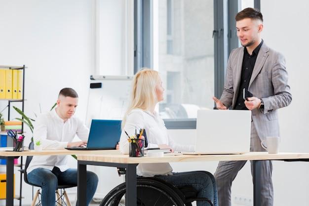 Vista lateral da mulher em cadeira de rodas, conversando com um colega de trabalho masculino