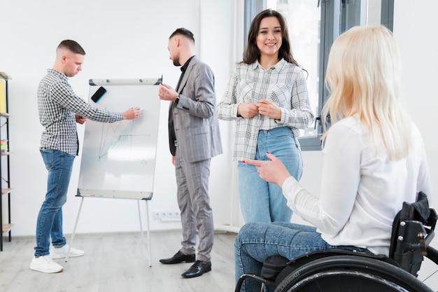 Vista lateral da mulher em cadeira de rodas, conversando com um colega de trabalho no escritório